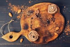 在一个木切板,顶视图的巧克力杯形蛋糕 奶油色杯形蛋糕 免版税图库摄影