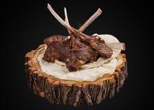 在一个木切片烤的放在架子上的羊羔 免版税库存照片