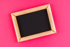 在一个木制框架的黑板与在桃红色背景的一个空的箱子 复制空间 免版税图库摄影