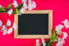 在一个木制框架的黑板与在桃红色背景的白花围拢的一个空的箱子 复制空间 的模板 免版税库存照片