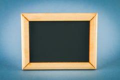 在一个木制框架的黑板与在灰色背景的一个空的箱子 复制空间 库存图片