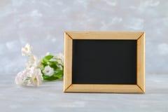 在一个木制框架的黑板与在灰色背景的白花围拢的一个空的箱子 复制空间 spri的模板 免版税库存图片
