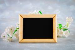 在一个木制框架的黑板与在灰色背景的白花围拢的一个空的箱子 复制空间 spri的模板 免版税图库摄影
