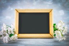 在一个木制框架的黑板与在灰色背景的白花围拢的一个空的箱子 复制空间 spri的模板 免版税库存照片