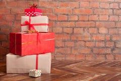 在一个木地板上的圣诞节礼物在砖墙背景 库存图片