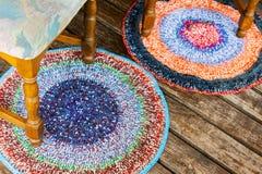 在一个木地板上的手工制造五颜六色的地毯 免版税库存图片