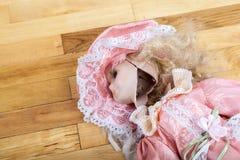 在一个木地板上的残破的玩偶 库存照片