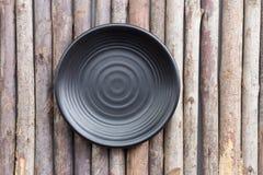 在一个木地板上的黑色的盘子 库存图片