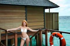 在一个木大阳台的年轻美好的妇女立场由在一lifebuoy附近的海在风暴天气 免版税库存照片