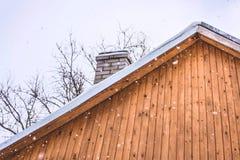 在一个木屋顶的降雪 蓝色分行休息日霜谎言天空雪结构树冬天 库存图片