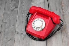 在一个木平台的红色减速火箭的转台式电话 图库摄影