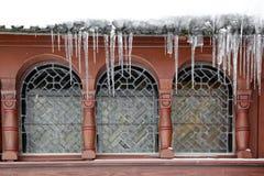 在一个木房子的冰柱有主角给上釉的窗口的 免版税图库摄影