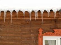 在一个木房子的屋顶的冰柱 免版税库存图片