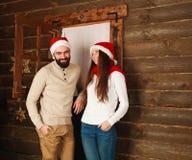 在一个木房子的背景的愉快的圣诞节夫妇 免版税库存图片