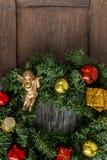 在一个木房子的门的圣诞节花圈 库存图片