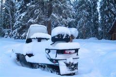 在一个木房子附近的斯诺伊雪上电车在森林 免版税库存照片