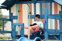 年轻在一个木操场的男孩坐的读书 免版税库存图片