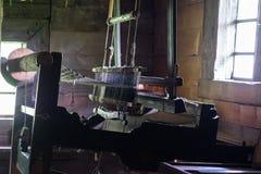 在一个木日志小屋的内部的古老编织机 免版税库存照片