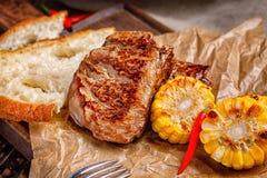 在一个木服务板的可口新鲜的油煎的牛排与金黄油煎的玉米切片和面包片 免版税库存照片