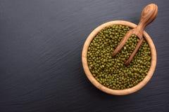 在一个木杯子和木瓢在黑石委员会背景,文本的,豆空间的绿豆 免版税库存图片