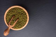 在一个木杯子和木瓢在黑石委员会背景,文本的,豆空间的绿豆 库存照片