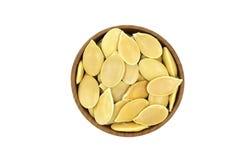 在一个木杯子的几粒南瓜籽 免版税图库摄影