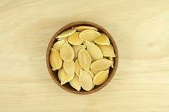 在一个木杯子的几粒金黄南瓜籽 库存照片