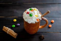 在一个木杯子的打好的奶油用桂香和颜色糖果棍子  免版税库存图片