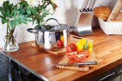 在一个木板刀子厨房工作台面,内部,平底锅,滚刀,烹饪器材的蕃茄 库存图片