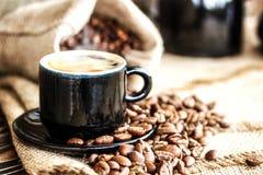在一个木板和一杯咖啡的咖啡粒 免版税库存图片