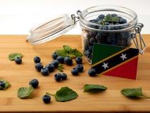 在一个木板条的圣克里斯多福与尼维斯旗子用蓝莓是 免版税库存照片