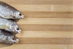在一个木板的三条干燥干鱼 免版税图库摄影