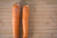 在一个木板的两棵新鲜的红萝卜 免版税图库摄影
