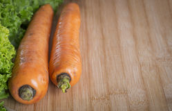 在一个木板的两棵新鲜的红萝卜 图库摄影