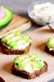 在一个木板的健康鲕梨和hummus三明治 素食主义者单片三明治 四旬斋菜单 垂直的照片 特写镜头 免版税库存照片