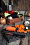 在一个木板的切好的红萝卜,在木箱的新鲜蔬菜在葡萄酒背景 免版税库存图片