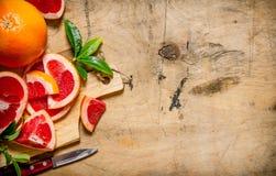 在一个木板的切的葡萄柚有叶子的 库存图片