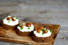 在一个木板的单片三明治 三明治用黑麦面包、软干酪、蘑菇和葱 免版税库存图片