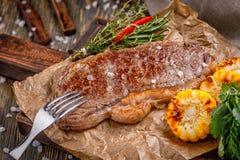 在一个木板的可口新鲜的油煎的牛排服务的与调味料和草本,油煎的肉一个大片断  免版税图库摄影