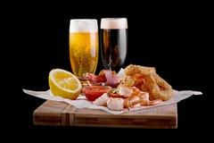 在一个木板的啤酒开胃菜戴啤酒两副眼镜在黑背景的 关闭 免版税库存照片