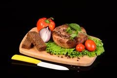 在一个木板的圆的肉牛排有菜的 免版税库存照片