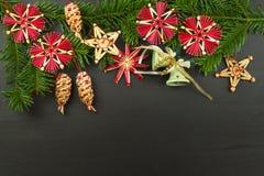 在一个木板的圣诞节装饰 抽象空白背景圣诞节黑暗的装饰设计模式红色的星形 圣诞节与装饰的杉树在一个木板 库存图片