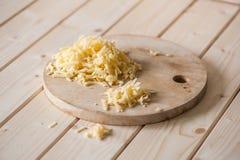 在一个木板的搓碎干酪 图库摄影