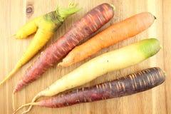 在一个木板的新鲜的五颜六色的红萝卜 图库摄影