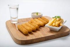 在一个木板的炸鱼排用调味汁和油煎的土豆 免版税库存照片