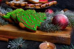 在一个木板的特写镜头说谎曲奇饼以圣诞树,玩具球,云杉的枝杈的形式 免版税图库摄影