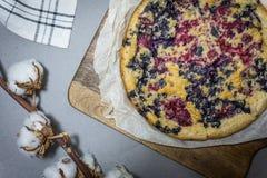 在一个木板的自创蓝草莓饼有棉花的在灰色背景开花 免版税库存图片