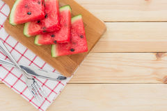 在一个木板的西瓜切片,服务与利器和餐巾在木表上 免版税库存图片