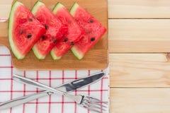在一个木板的西瓜切片,服务与利器和餐巾在木表上 库存图片