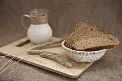 在一个木板的面包和牛奶 免版税图库摄影